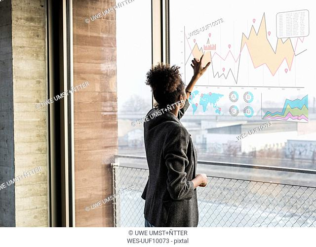 Young woman touching windowpane with graph in office