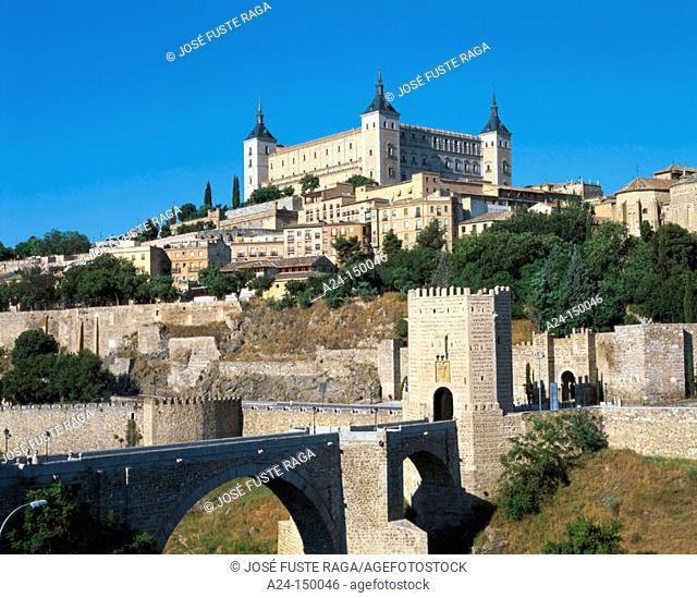 Alcántara bridge and Alcázar fortress dominating the city in background. Toledo. Spain