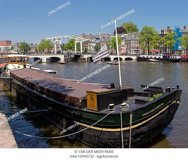 Inland cargo ship on the river Amstel near the Skinny Bridge