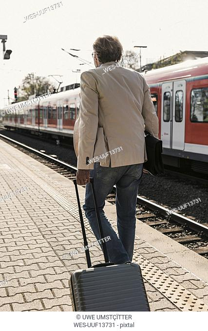Rear view of mature businessman walking at train platform with suitcase