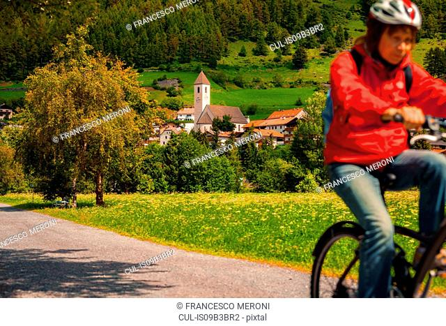 Senior woman cycling along village path in Vinschgau Valley, South Tyrol, Italy