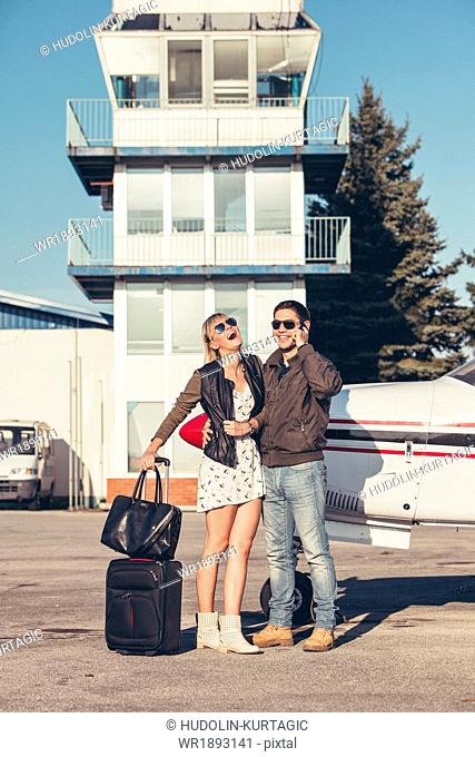 Young couple with luggage by propeller airplane, man using phone