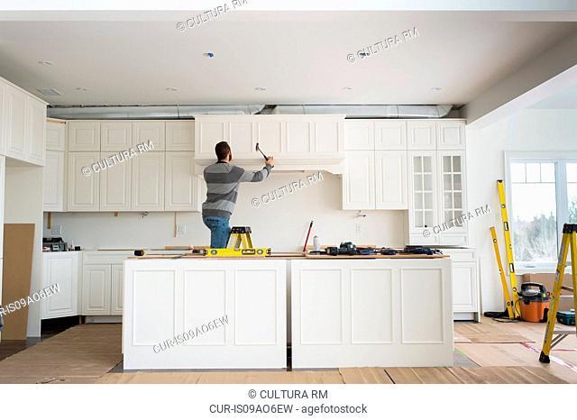 Carpenter installing kitchen cabinet