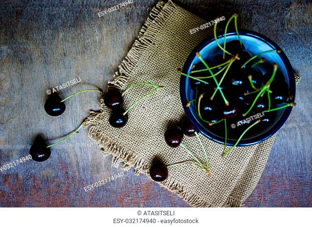 Ripe sweet cherries in the bowl on the rustic style old table