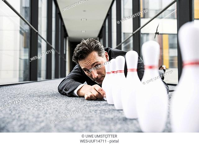 Diligent manager lying on the floor in office passageway adjusting pins