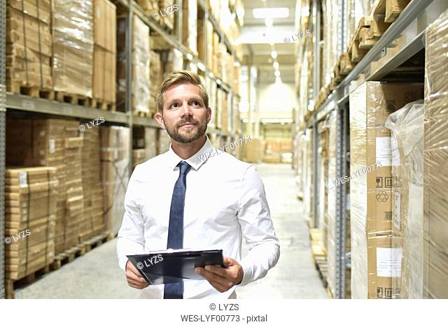 Businessman with clipboard in warehouse looking at shelves