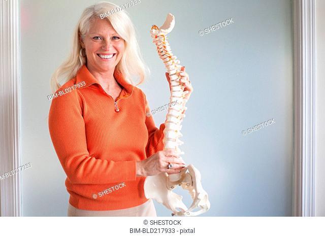 Caucasian chiropractor holding model spine