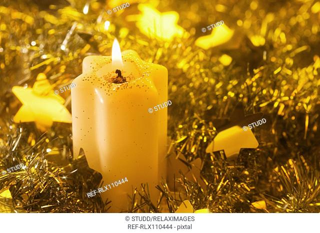 Lighted candle arrangement surrounded by Christmas decorations
