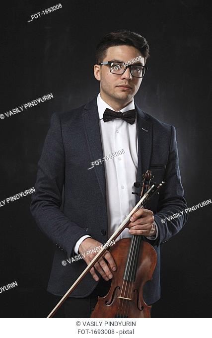 Portrait of confident young man holding violin while standing against black background
