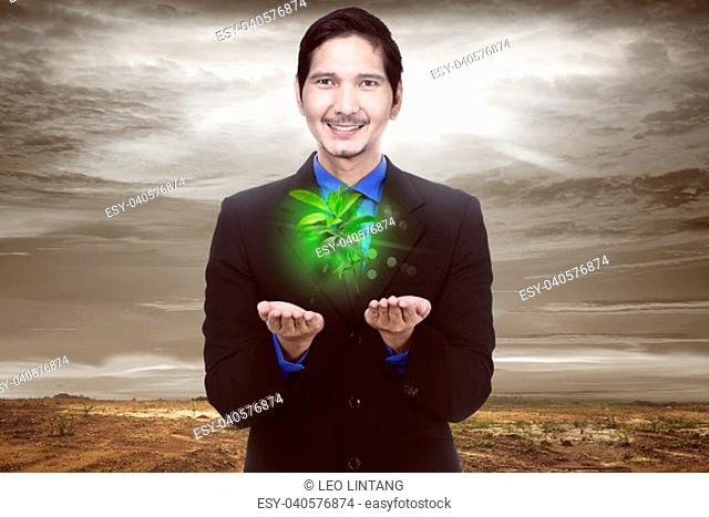 Handsome asian businessman holding plant with climate change background