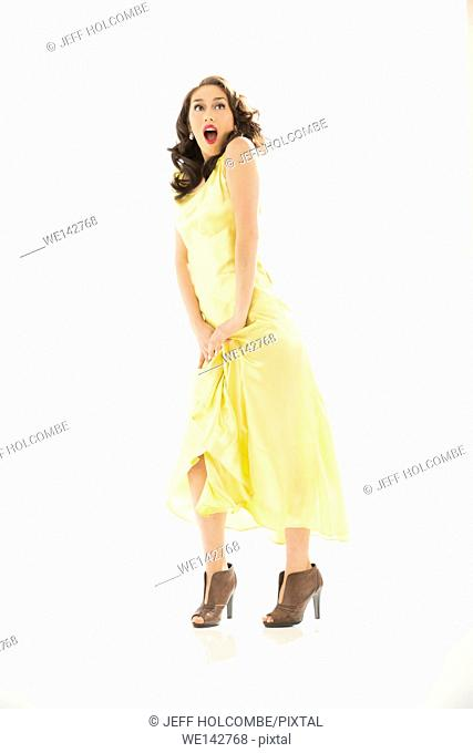 Beautiful young woman shocked in vintage yellow dress, full length in brown heels