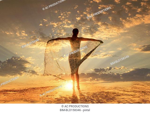 Caucasian woman under dramatic sunset sky