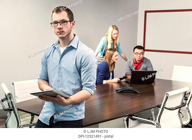 Young millennial business man posing for the camera in a conference room of young professionals working together in a modern place of business; Sherwood Park