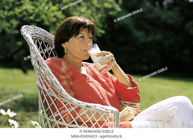 Woman sits in the garden and drinks a glass of milk