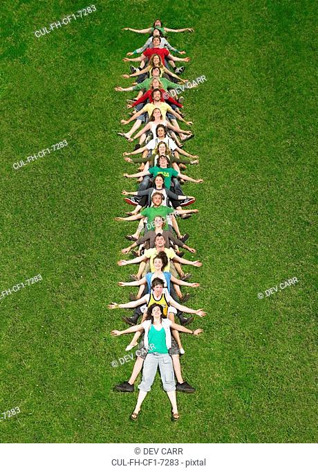 Group lying back on each other in a line on grass