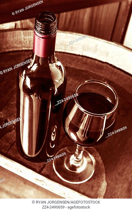 Elevated still life photograph of an old style wine bottle and glass on rustic wine cellar barrels. Luxury liquor