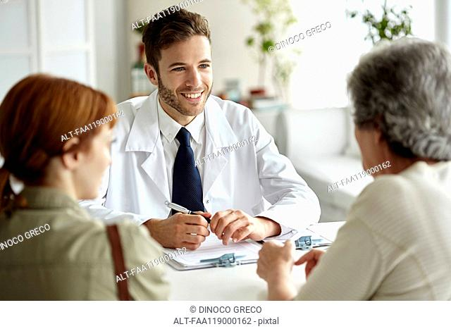 Smiling doctor talking with senior patient