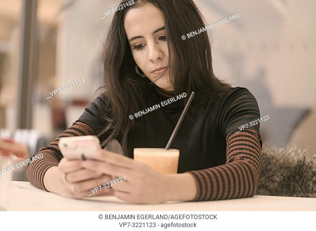portrait of woman typing text message with phone while taking a break with juice glass at table in café, in Munich, Germany