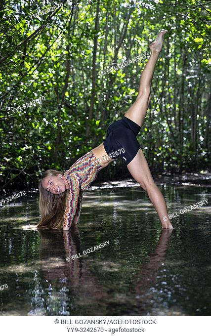 Young woman doing a yoga pose (Downward Facing Dog Split (Three-Legged Dog) in a natural setting - Fort Lauderdale, Florida, USA