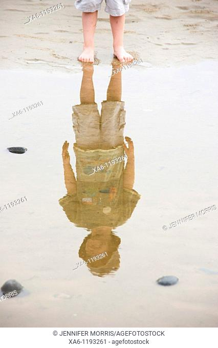 A boy's legs and his reflection in a puddle on the beach