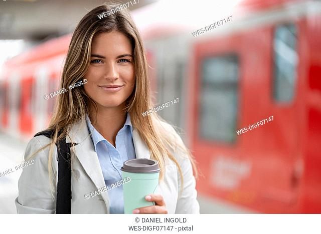 Young businesswoman with coffee to go cup, standing on station