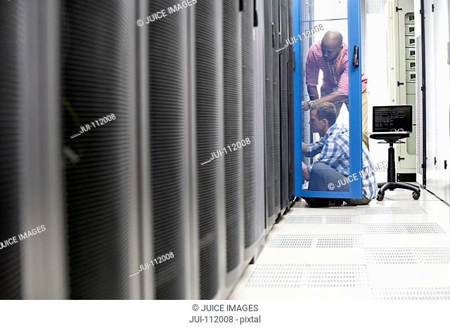 Technicians with laptop checking server in data centre