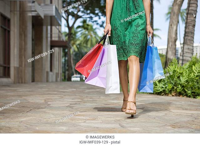 Low section of a woman walking with shopping bags