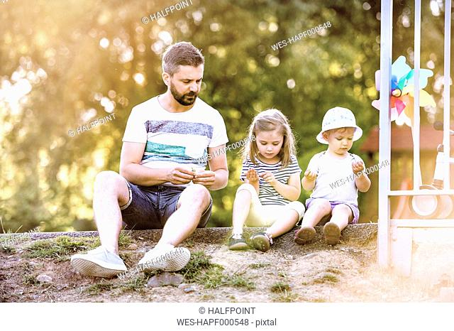 Father and his little daughters sitting side by side on the ground in a park