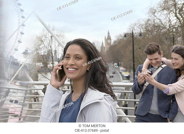 Smiling woman talking on cell phone on urban bridge, London, UK