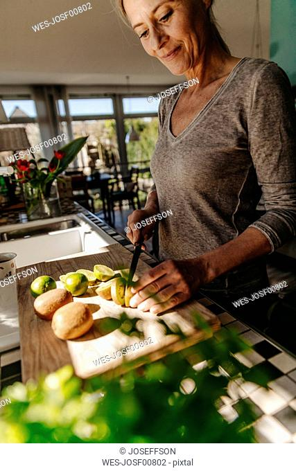 Woman in kitchen cutting limes and kiwis
