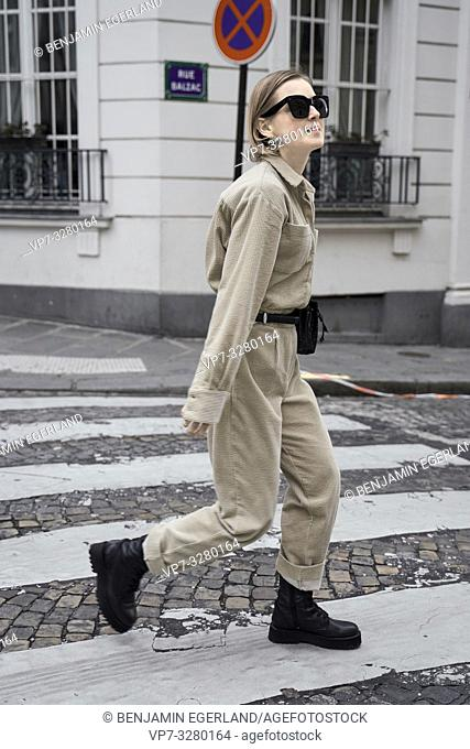 fashionable woman crossing street at zebra crossing during fashion week, in Paris, France