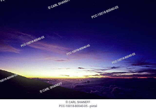 Hawaii, Pink and purple sky seen from high mountaintop above the clouds at sunset