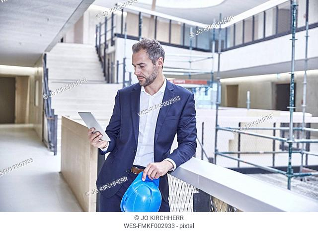 Architect in office building looking at tablet