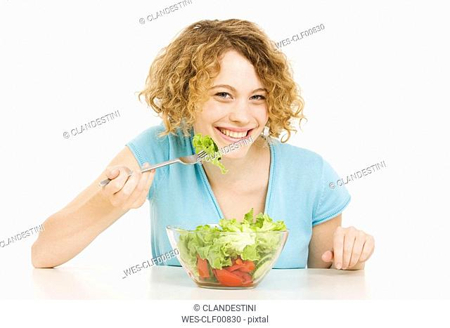Young woman eating salad, smiling, portrait