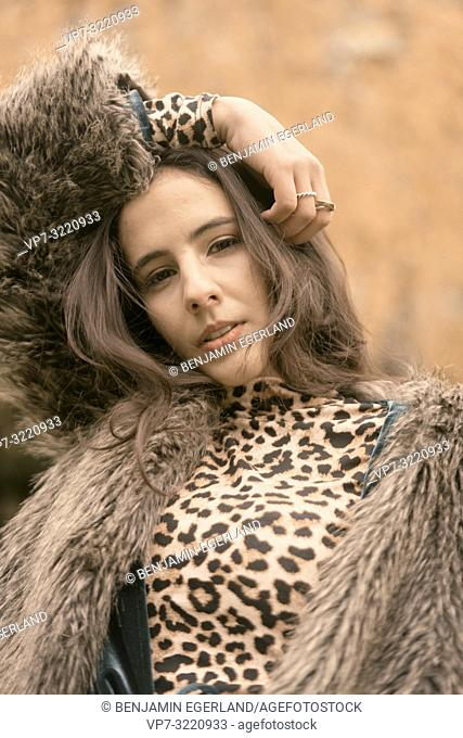 headshot of fashionable woman playing with hairs, autumn season, sensual, in Munich, Germany