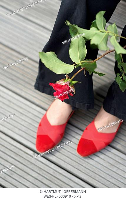 Woman with red rose wearing pair of red shoes
