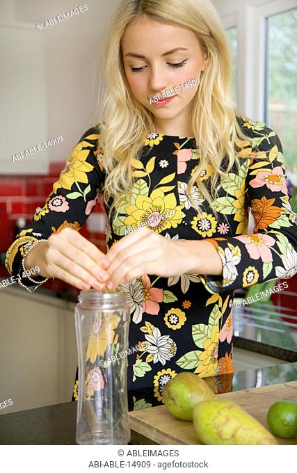 Young Woman Making Fruit Smoothie
