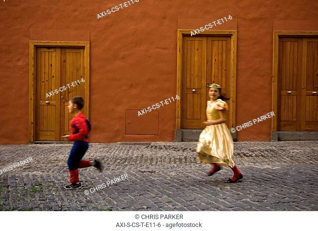 Children 5-7 running in street at International Carnival of Puerto de la Crux in Gran Coso Apoteosis