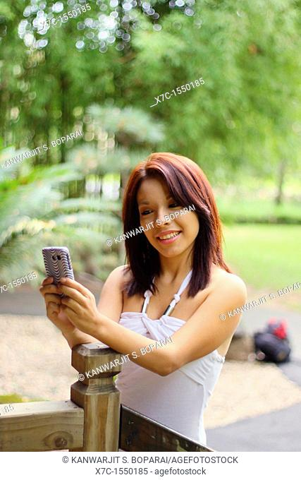 A beautiful young lady enjoying her smartphone