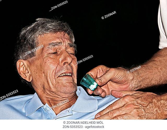 Arzt gibt einem älteren ängstlichen Patienten Tabletten Doctor giving a fearful older patient tablets