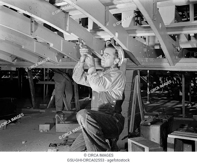 Carpenter Building Torpedo Boats at Shipyard during WWII, New Orleans, Louisiana, USA, Howard R. Hollem for Office of War Information, July 1942