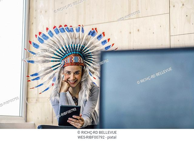 Young woman wearing Indian headdress, standing in office, using digital tablet