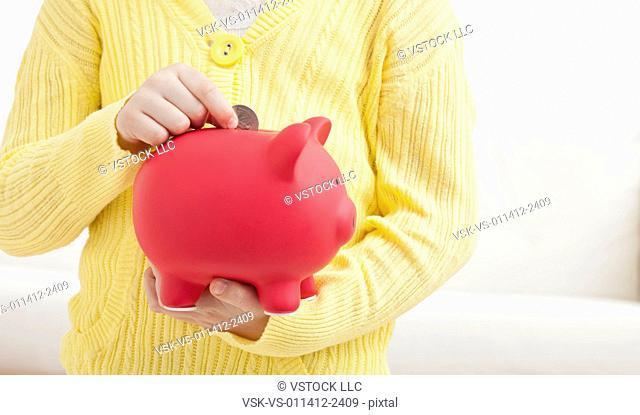 USA, Illinois, Metamora, Girl (6-7) holding red piggybank