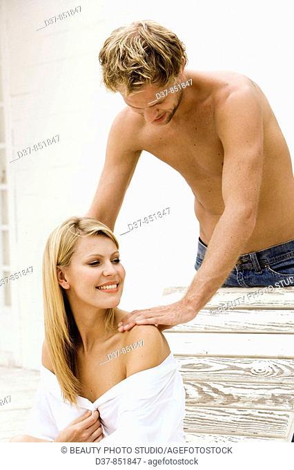 Man massaging a woman at home