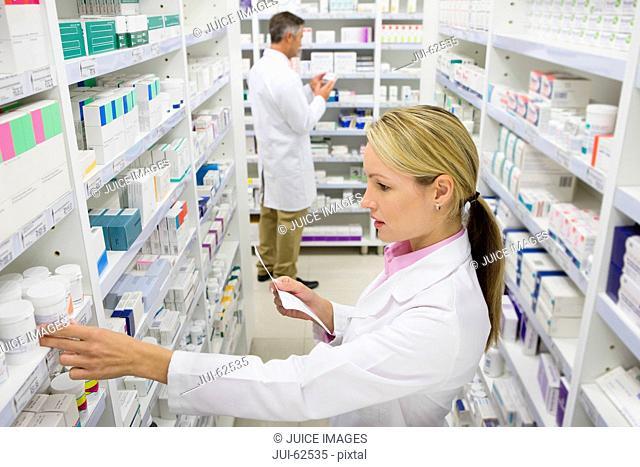 Pharmacist searching for medication on pharmacy shelves