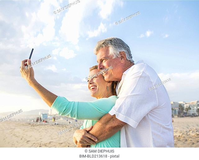 Caucasian couple taking cell phone selfie on beach