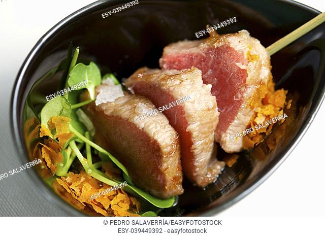 Tuna belly in a small black bowl