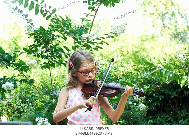 Hispanic girl playing violin outdoors
