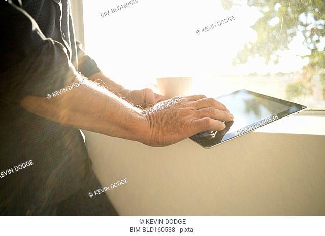 Hispanic businessman using digital tablet near window