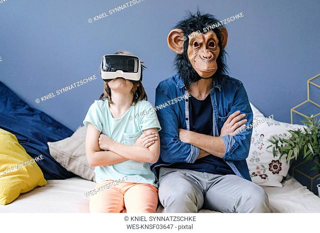 Father wearing monkey mask sitting next to son wearing VR glasses at home